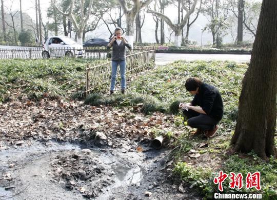 图为:杭州数字城管采集员现场调查污水直排情况。