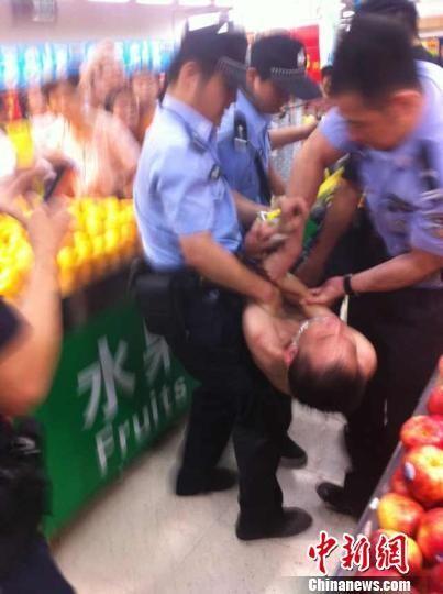 图为警方将持刀男子擒获。