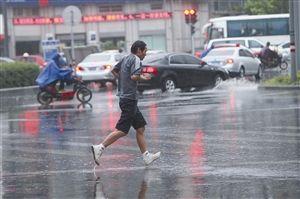 月21日傍晚,新马路上一位没带雨具的男士冒雨奔跑 记者 贾东流 摄