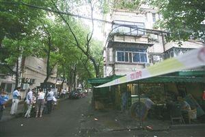 昨日,徐戎一村26-28号房屋外拉起了警戒线。警戒线外,附近居民如往常般打牌娱乐。