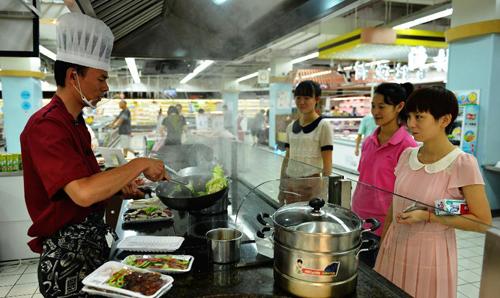 """8月14日,在杭州一家超市,""""代烧菜肴""""的厨师忙着为高温天不愿下厨的顾客烹制菜肴。新华社发(龙巍 摄)"""