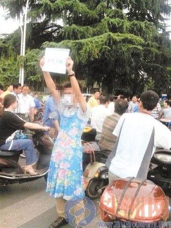 对公司的新着装规定,有男员工穿长裙举牌抗议(图片来自微博)