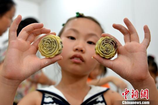 小朋友展示DIY的带有玫瑰花图案的月饼。 王思哲 摄