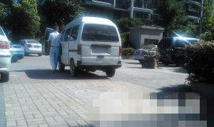 法拉利开走,车主推着面包车往前挪,继续占车位。  记者 董吕平 摄
