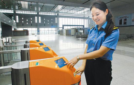 在高铁绍兴北站,工作人员正在演示进站闸机的使用方法。 (记者 黄霄 摄)