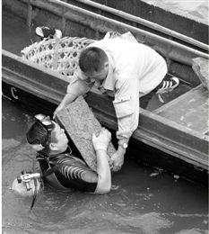 8月22日清晨,蛙人在西泠桥下打捞被撞落西湖的护栏石。 本报记者 董旭明 摄