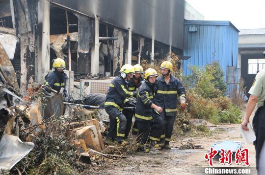 消防人员将一名火灾伤亡者紧急抬出。