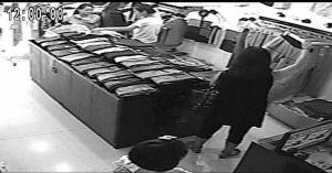 监控显示,小女孩走向收银台时,俩大人在一边掩护。