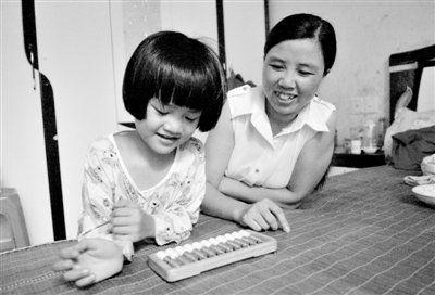8月9日,喊雪在家中教女儿打算盘计算加减法。晓强 摄