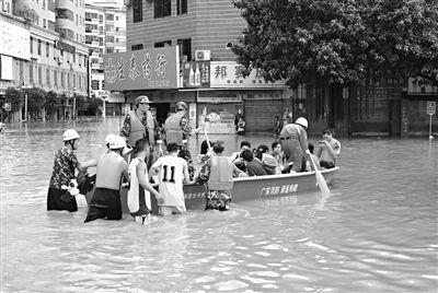 18日,广东省清远市阳山县县城,消防官兵合力推动冲锋舟,转移被困学生。新华社发