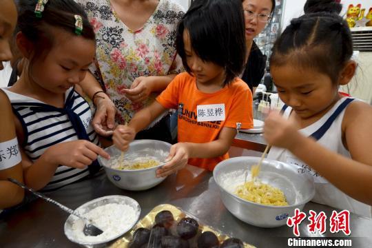 小朋友用木棒搅拌碗里的面粉。 王思哲 摄