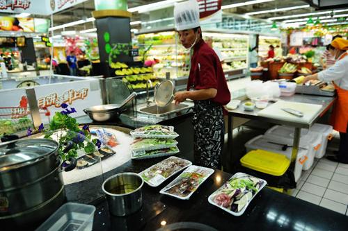 """8月14日,在杭州一家超市,厨师准备为顾客""""代烧菜肴""""。新华社发(龙巍 摄)"""