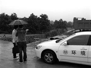 环保部门工作人员正在查看河道 记者 陈善君 摄
