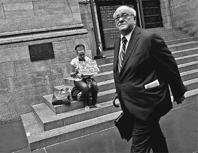 美国纽约街头,一位商人从一位当街乞讨的妇女面前经过。