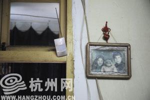 装在李奶奶家门栓处的感应器和墙上的一张老照片。 记者 韩丹 摄
