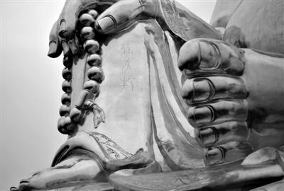 """千灵山风景区,距地约4米高的弥勒佛腿部,被刻上的""""徐东辉""""三字清晰可见。新京报记者 王叔坤 摄"""
