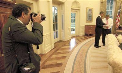 索萨正在拍摄奥巴马与官员交谈。