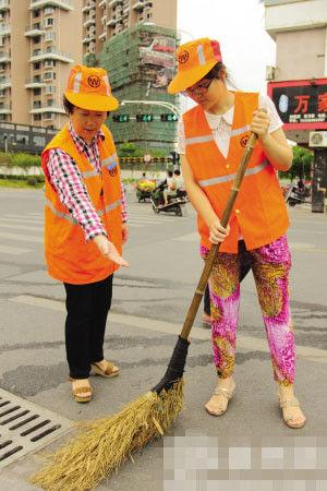 徐爱萍在指导新人怎么握扫把