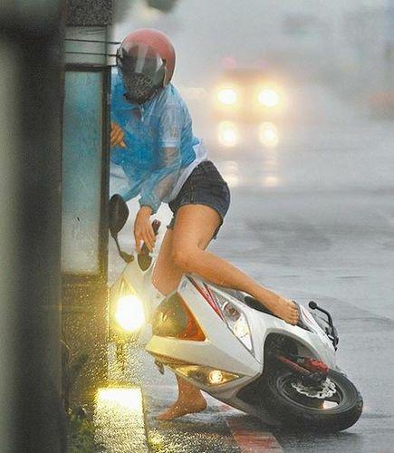屏东恒春街头一名女骑士被强风吹往路旁,几乎抓不住摩托车。图片来源:台湾媒体