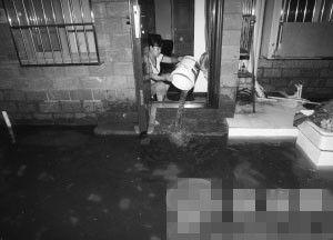 下马塍小区,一居民用水桶往外舀水。 记者 方晟 摄