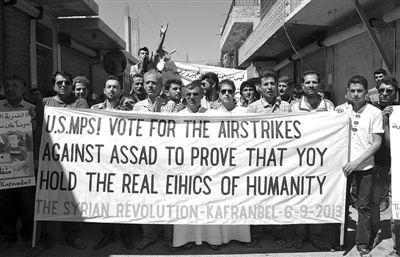 6日,叙利亚西北部的民众打出横幅,要求美国对叙动武。