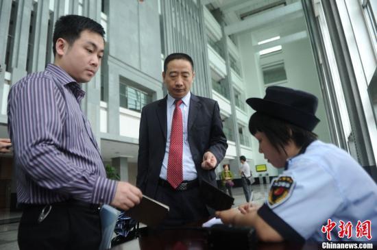 """9月5日,备受关注的重庆不雅视频案件二审在重庆市第一中级人民法院不公开开庭审理。记者在重庆市第一中级法院见到赵红霞的代理律师张智勇。据张智勇介绍,赵红霞在一审宣判后没有提出上诉。但根据新刑事诉讼法323条规定""""对同案审理案件中未上诉的被告人,未被申请出庭或者人民法院认为没有必要到庭的,可以不再传唤到庭""""。图为赵红霞的代理律师(左二)进入法院。陈超 摄"""