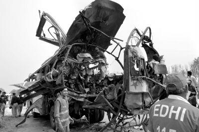 9月27日,人们在巴基斯坦西北部城市白沙瓦的爆炸现场检查遭袭班车。新华社发