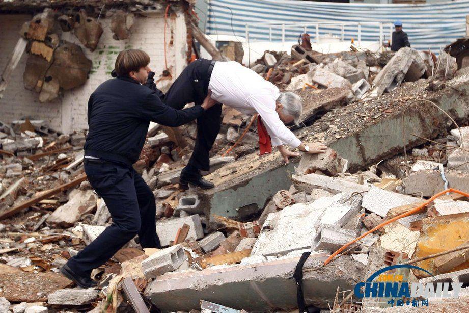 当地时间2013年8月30日,智利圣地亚哥,智利总统皮涅拉在视察一处拆迁工地时,绊倒在瓦砾堆上。