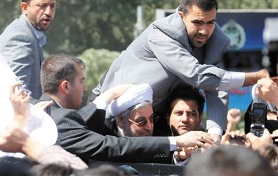 28日,德黑兰,伊朗总统鲁哈尼遭扔鞋后,在保镖护送下离开机场。