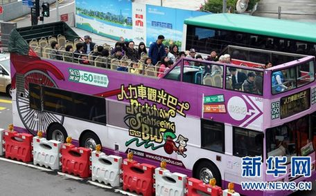 一些内地游客在香港中环乘坐观光巴士游览(1月27日摄)。当初旨在拉动香港经济发展的而推出的内地赴港个人游,已走过10个年头,这一过程虽然出现过一些波折,但此间观察人士和从业者则指出,对香港的经济和就业而言,未来仍需要内地庞大而稳定的旅游客流。新华社记者 李鹏 摄