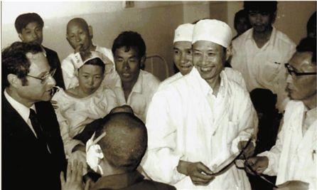他一进病房,病人就围了上来。咧嘴笑的这位清瘦的医生,就是陶祥洛。(摄于上世纪80年代)