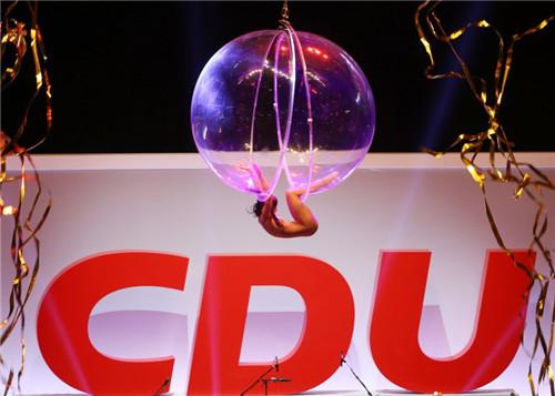 美女在裂开的球体内展示悬挂的动作。