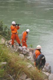 8日上午,消防官兵在江边搜寻失踪者。