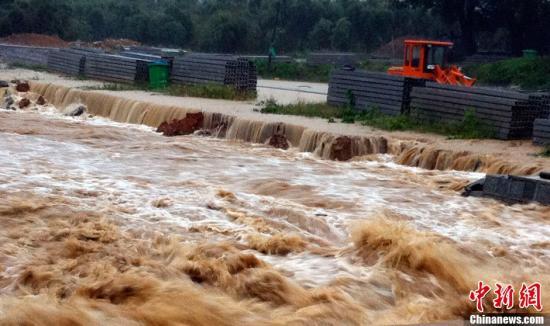 """10月7日,急流的河水冲垮堤坝。据了解,受强台风""""菲特""""带来的暴雨天气影响,浙江德清县上柏山民村一条河流因水流湍急,冲击力强,将7月刚修筑的堤岸冲垮。河水瞬间涌上路面,干道上完全无法行车。中新社发 张骏 摄"""