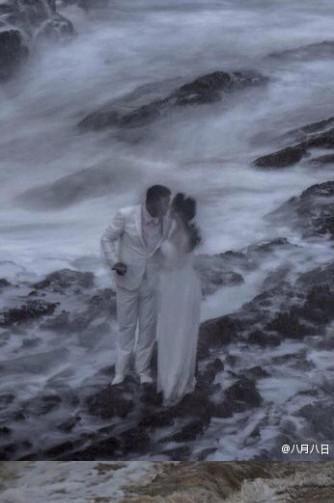 情侣不惧狂风巨浪海边拍婚纱照