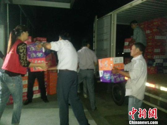 图为志愿者在发放物资。 徐小勇 摄