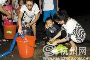 昨晚7点,新明半岛小区,居民们在楼下接水洗菜。记者 胡聪 摄