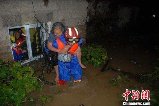 图为救援人员蹚水背民众离开。 黄海 摄