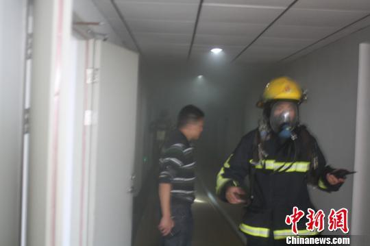 图为消防队员在救援。 伍晓阳 摄