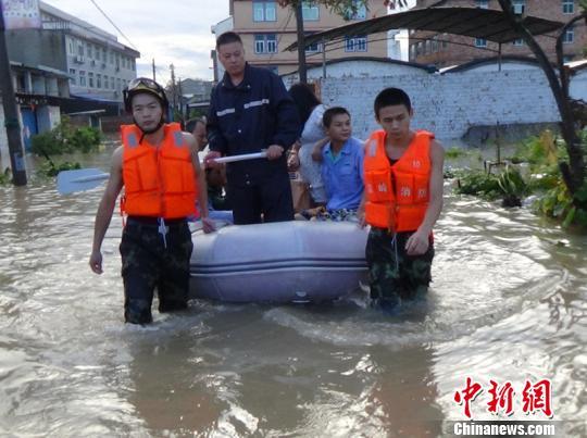 图为救援人员蹚水帮助民众离开。 黄海 摄