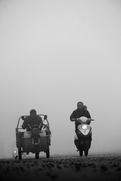 9月30日,河南省安阳市内黄县群众在雾霾中骑行