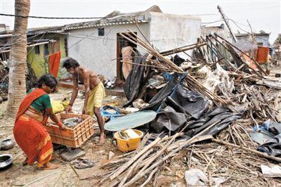 13日,奥里萨邦,村民在风暴过后的废墟中寻找他们的财物。
