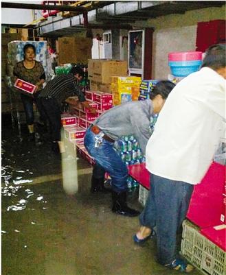 店员们在转移超市地下室货物。 邵巧宏 摄