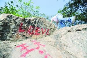 山壁岩石上喷涂着各种字迹。记者 张华 摄