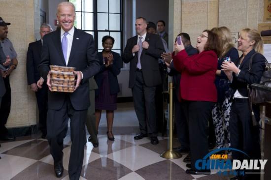 当地时间2013年10月17日,美国华盛顿,副总统拜登带着松饼迎接重返工作岗位的环保署员工。美国政府在关门16天之后重新开门,政府职员重返工作岗位。