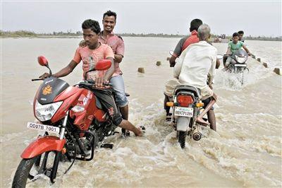 13日,奥里萨邦,当地民众骑摩托车在洪水中行进。
