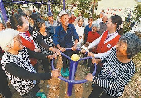 """重阳节前夕,志愿者在睢宁县""""农村老年人关爱之家""""与留守老人游戏互动。万程鹏摄"""