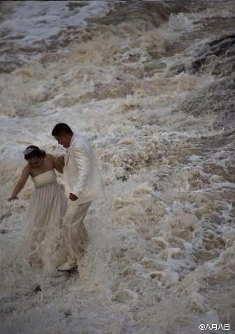 情侣全然不顾风浪袭击 海边拍婚纱照