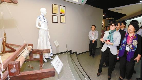 浙商博物馆正式开馆。万事利集团董事长屠红燕在老织布机前当起了临时解说员。 记者 董旭明 摄