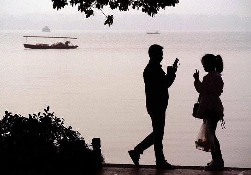 11月4日,一对男女青年在西湖边拍照留影。 新华社记者王颂摄